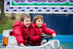 Two boys, riding boat in amusement park - stock photo