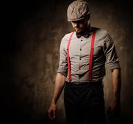 Serious old-fashioned man in tweed hat wearing suspenders and bow tie, posing Stock Photos