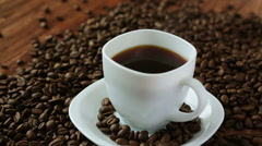 Flavored coffee in cup surrounded by coffee beans Stock Footage