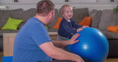 A small child is hitting a big blue ball Stock Footage
