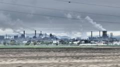 Apocalyptic view at smoking chimneys nex to farmland. Air and soil contamination - stock footage