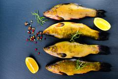 top view of fresh tench fish with aromatic herbs, spices and vegetables on sl - stock photo