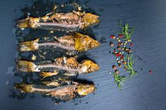 Top view of fish skeleton bones and flavor peppers on slate background, close Stock Photos