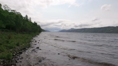 Aerial shot along the coast of Loch Ness in the Scottish highlands Stock Footage