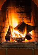Burning firewood in fire-box of fireplace Stock Photos