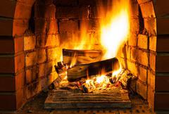 Burning firewood in brick fireplace Stock Photos