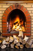 stack of wood and fire in indoor brick fireplac - stock photo