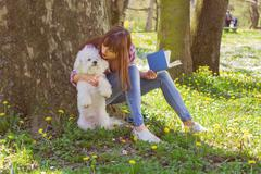 Beautiful young woman reading a book. Leisure time with her dog in the park. - stock photo