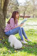 Beautiful young woman reading a book. Leisure time with her dog in the park. Stock Photos