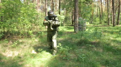 Paintball player in shooting at an opponent who hid behind an obstacle. Stock Footage