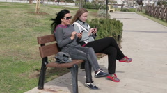Two young woman using a smart phone, outdoors on sitting on the wooden bench in Stock Footage