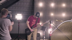 Behind the scenes. An operator film a scene of musical video with rock band on s - stock footage