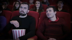 Man disturbs another person by talking in cinema - stock footage