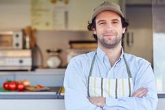 Small business owner smiling in front of his takeaway food - stock photo