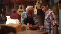 7-Old Lute Maker Teaching Grandson Boy Chiseling Wood - stock footage