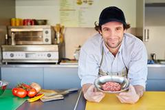 Food entrepeneur looking pleased with his quality hamburger meat Stock Photos