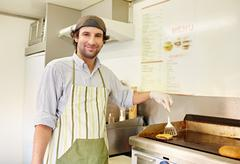 Male fry cook frying a fresh hamburger patty with cheese Stock Photos