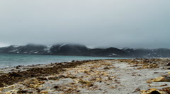 Timelapse small waves on arctic beach with mountains across bay - stock footage