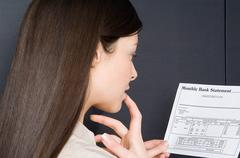 Woman looking at bank statement - stock photo