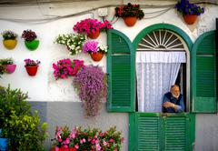 Bari, Italy. May 9, 2015: man looking out the door of his house with the faca - stock photo