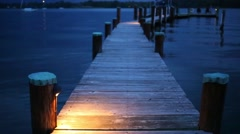 Wooden poles of pier at lake and ripple on water at night Stock Footage