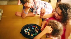 Woman with two children play game with rubber balls on table Stock Footage
