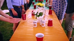 Table with Miller Lite beer and hands of people playing with glasses Stock Footage
