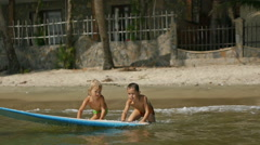 Little children enjoying sea surfboarding Stock Footage