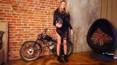 Pretty woman in black dress stands near moped in studio Stock Footage