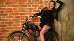 Pretty woman in black dress poses on moped in studio Stock Footage