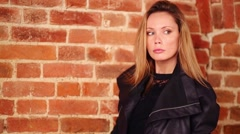 Pretty woman in leather jacket poses near red brick wall in studio Stock Footage