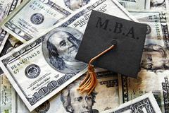 MBA grad rad cap on cash - stock photo