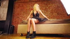 Pretty blonde woman in black dress sits on bed in studio - stock footage