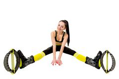 smiling young woman in a kangoo jumps shoes sitting  legs apart. - stock photo