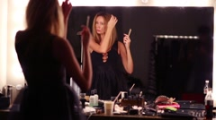 Pretty woman combed and looks in big mirror in dressing room Stock Footage