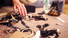 Female hand picks fashionable jewelry on bed. Close up view Stock Footage