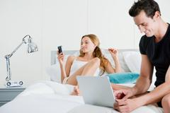 Couple on bed with laptop and handheld computer Stock Photos