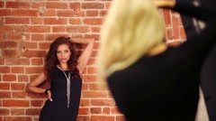 Woman poses near wall and back of shooting photographer out of focus Stock Footage