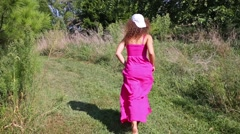 Pretty woman in pink dress runs on grass into bushes in garden Stock Footage