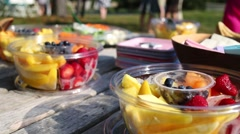Closeup view of various fruits in bowls on table outdoor Stock Footage