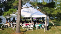 People under marquee at festival in green garden with pool Stock Footage