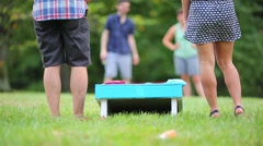 Back of legs of man and woman playing bean-bag toss game outdoor Stock Footage
