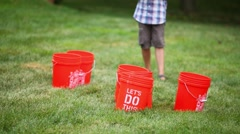 Boy stands next to red buckets and balls fall into bucket Stock Footage