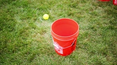 Red buckets and falling balls and legs of running boy outdoor Stock Footage