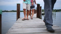 Legs of people going on wooden pier at lake in evening Stock Footage