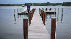 Pier with sitting people on silent lake with boat and sailboats Stock Footage