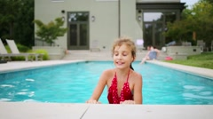 Happy girl in red swimsuit rests in outdoor pool near house Stock Footage