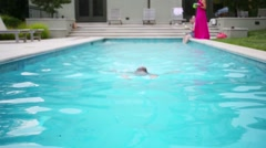 Girl swims in outdoor pure pool near house and people out of focus Stock Footage