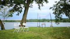 Green lawn and white tent for wedding next to scenic lake Stock Footage