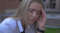 Girl sitting on the bench. She has a terrible headache. Close up. Urban Stock Footage